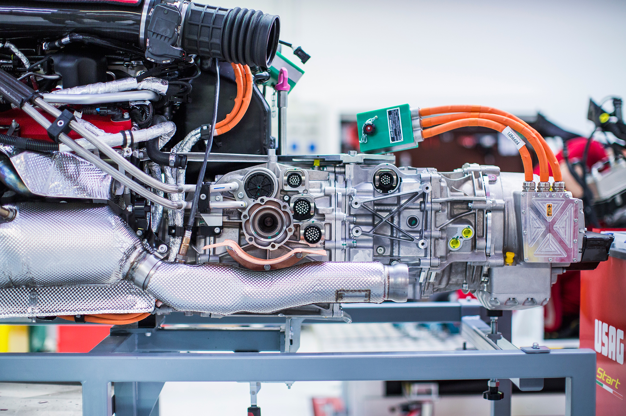 The V-12 engine is there, the seven-speed dual-clutch gearbox is there, and the electric motor is there, waiting expectantly for the electric inverters to be attached to its orange cables.