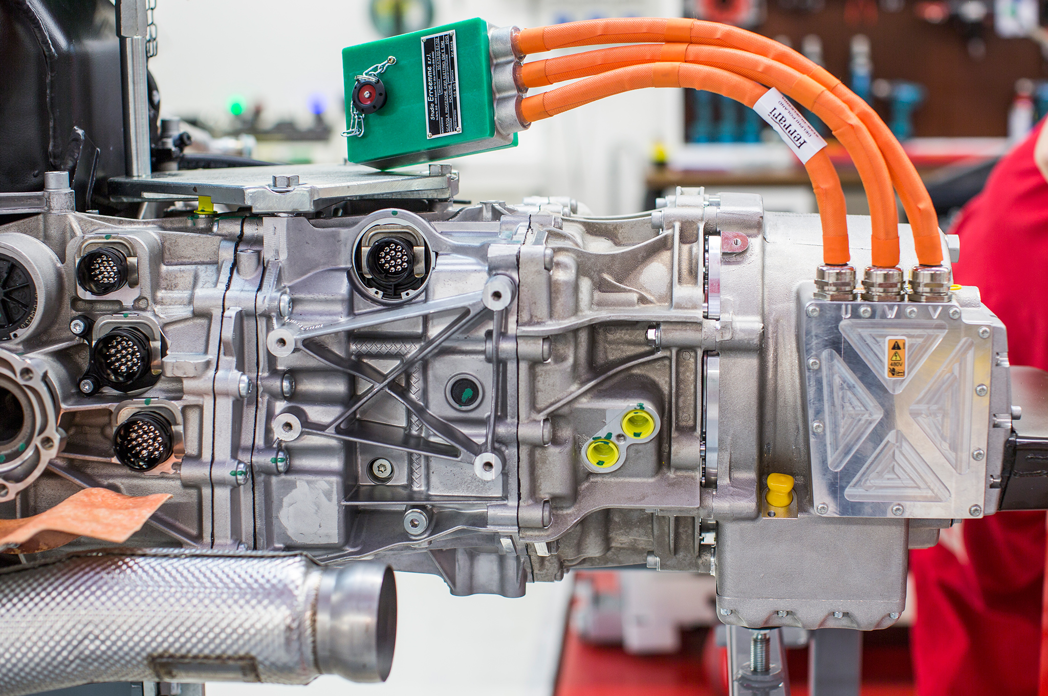 At the very rear of its chassis, aft of the V-12 engine and the seven-speed dual-clutch gearbox, resides the LaFerrari traction/generator electric motor, here with three orange power cables that will be attached to electric inverters.