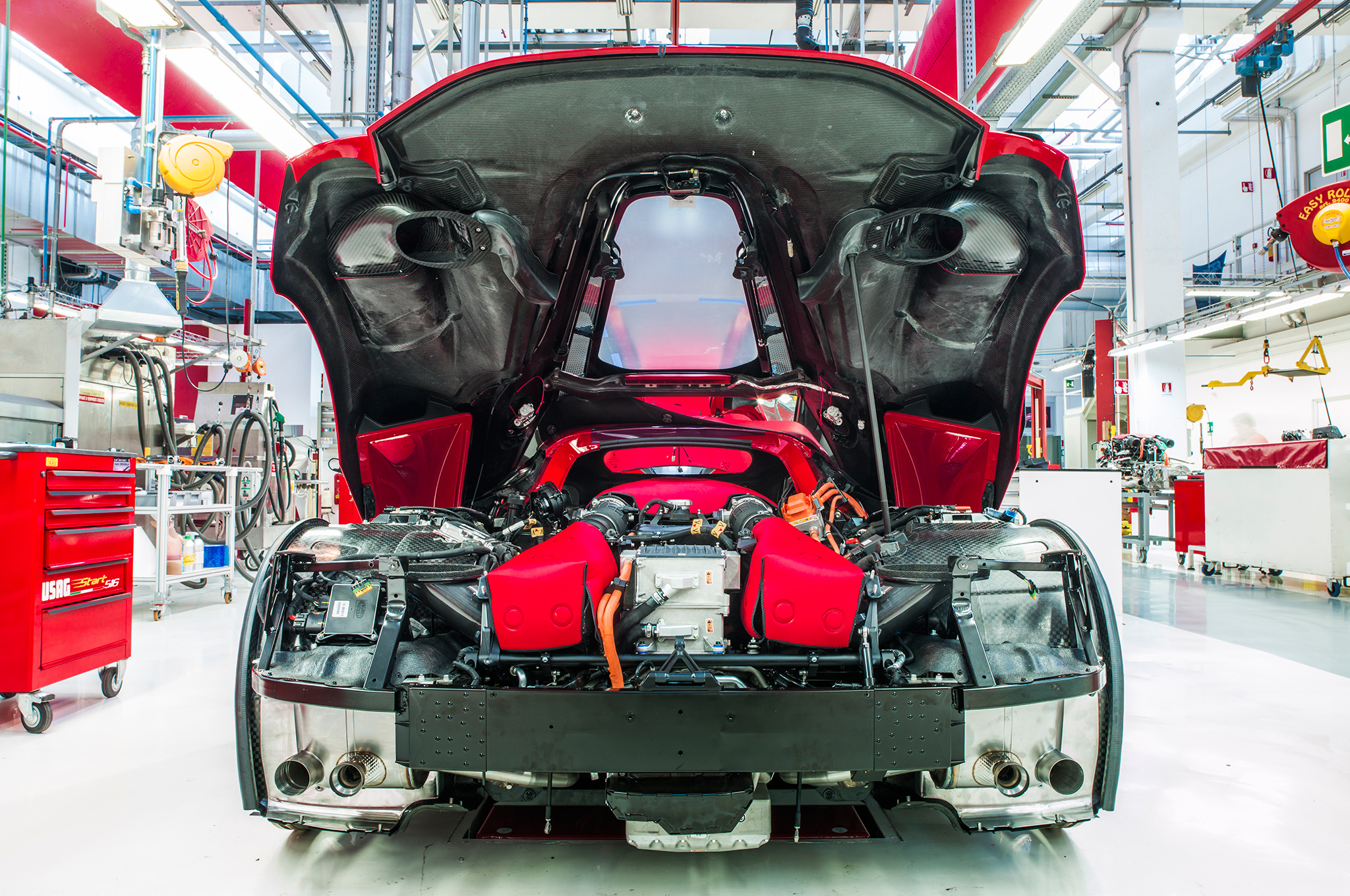 Not a single wasted millimeter, we were told by Ferrari engineers. No kidding: look at the powertrain components packed into the rear of LaFerrari. Silver-colored electric inverters (nestled between pieces of protective red fabric) lead to the heart of the beast, the 6.3-liter V-12.