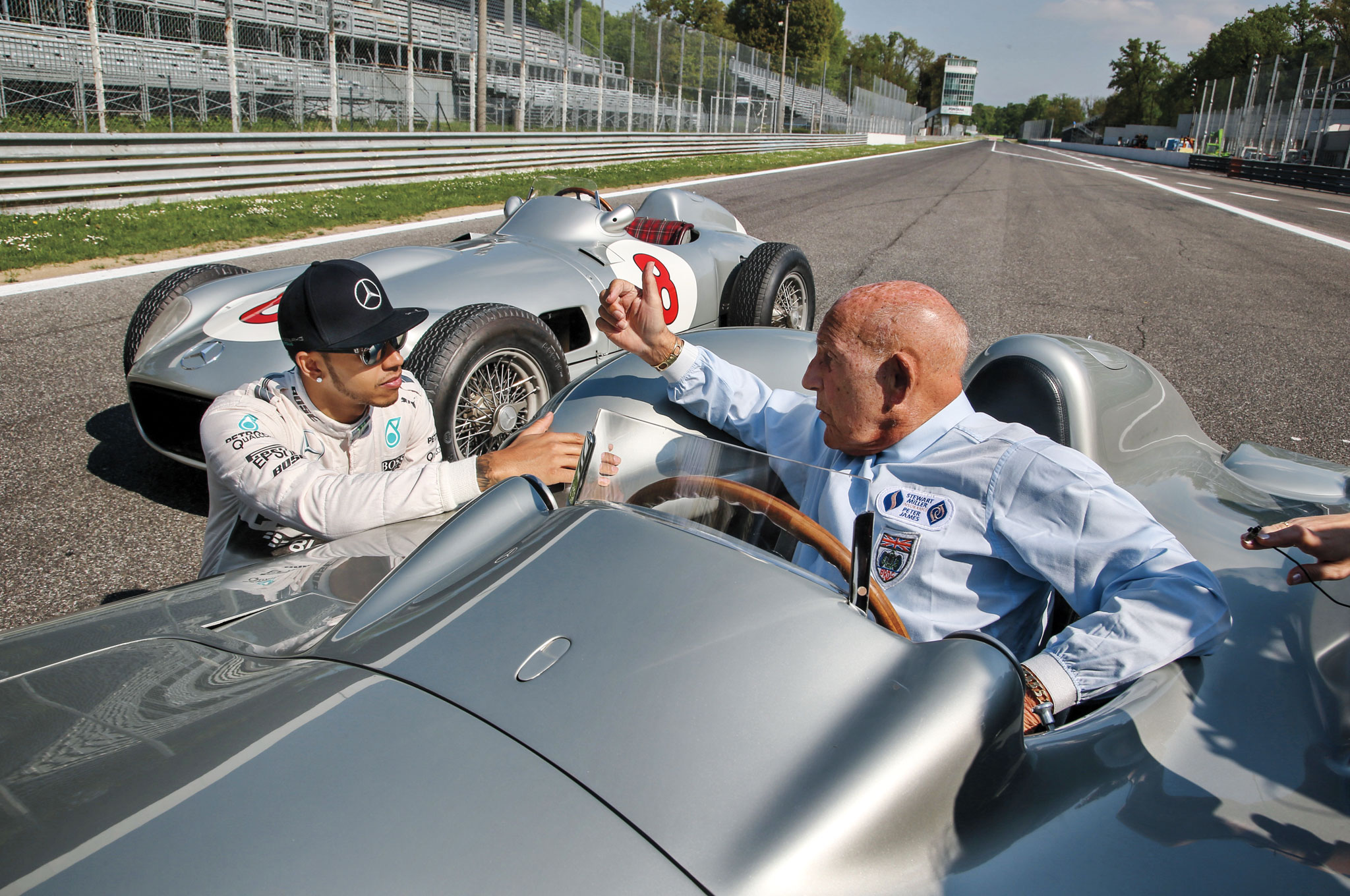 """Moss, the """"greatest driver to never win the Formula 1 world championship,"""" speaks with an attentive Hamilton, who has won two F1 titles, the first in his sophomore season."""