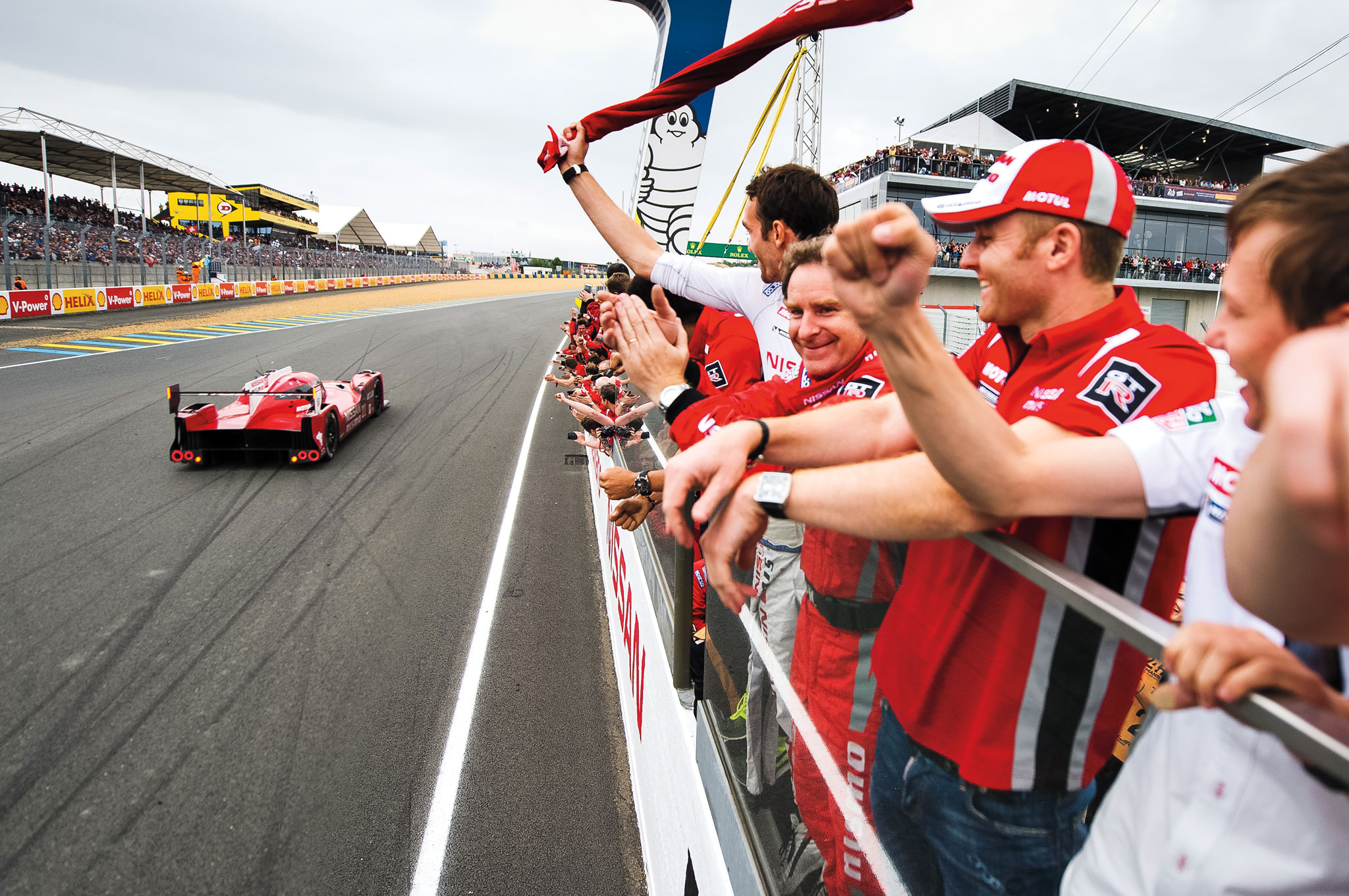 The Nissan team cheers after its  No. 22 GT-R LM NISMO, one of its three prototype cars at Le Mans, sees the checkered flag.