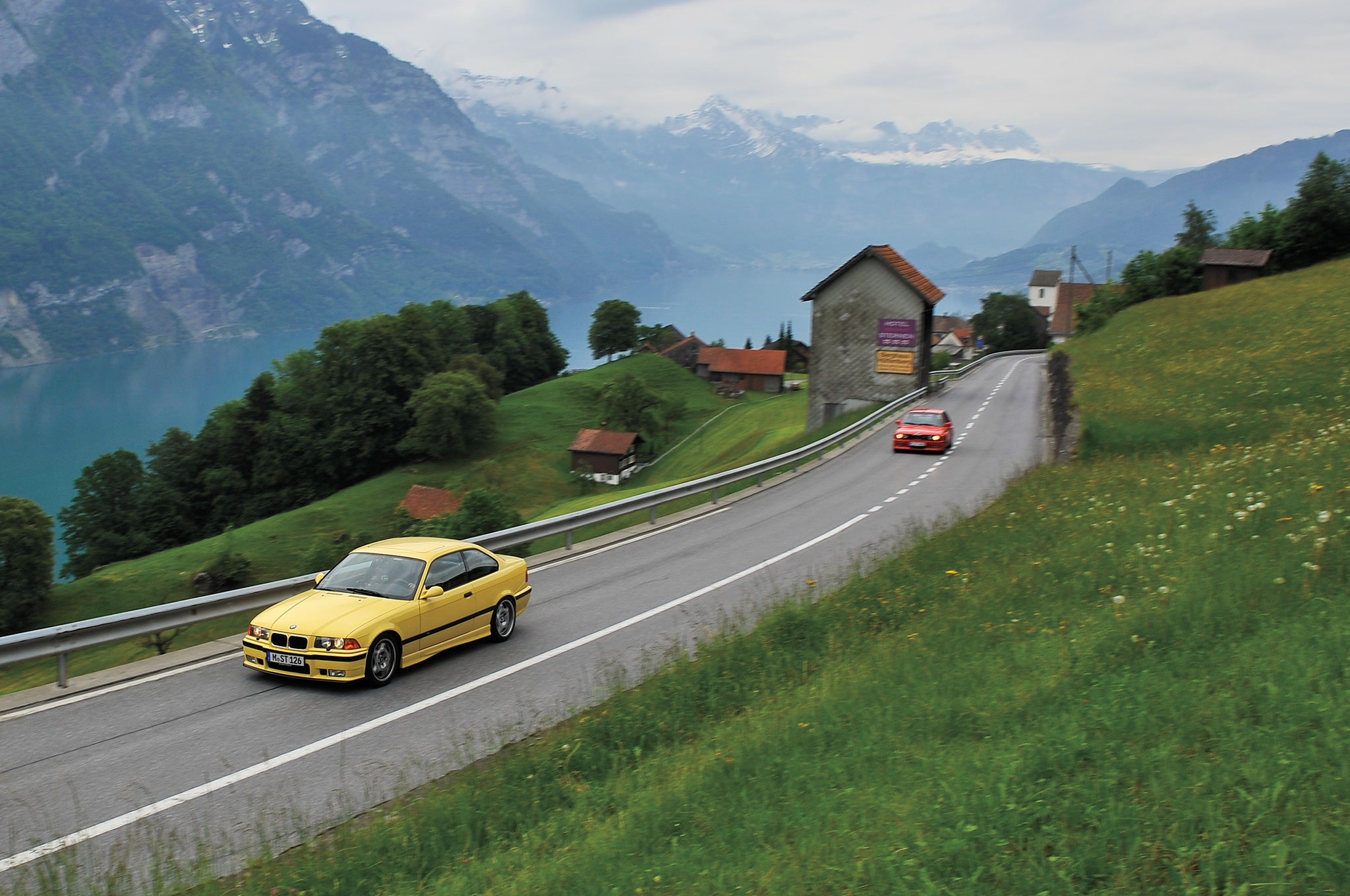 An alpine idyll of winding roads, agile cars, and snow flurries on a summer's day.