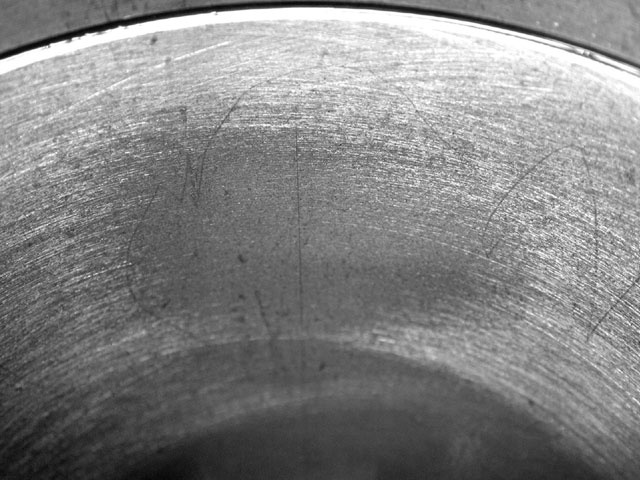 Torque plates really do make a difference. Jim lightly honed a bore, and then pulled the Sunnen hone head out of the bore. The distortion created by the head bolt load was clearly visible in the bore. The bores pulled out .001-inch under the bolt locations, or .0005-inch per side, visible as the dark area here where the hone skipped over the depressed area. Once honed out to final size, the bore will be perfectly round with the heads bolted on.