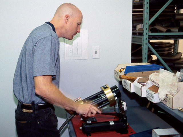 Scott Heintz uses XRP's special press to crimp the fittings in place.