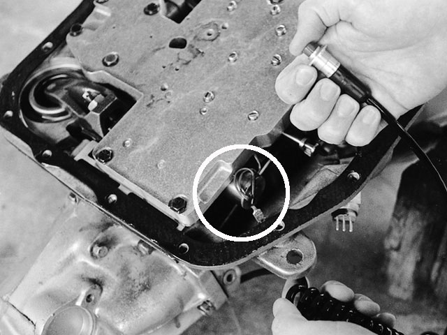 The specially cast and machined TCI trans-brake valve body is available separately so it can be added to your existing transmission. The electric trans-brake solenoid (circled) directs hydraulic pressure to engage Reverse and First whenever the microswitch button is depressed.