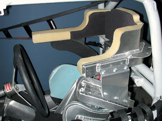 Aluminum outer support material is an economical alternative to carbon fiber, thus making this superior headrest design available to lower racing classes. Note the aluminum structure panels on both sides that link the headrest with the shoulders. These are critical for best operation.