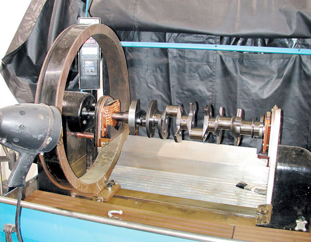 This is a typical setup for a horizontal bath magnetic particle inspection unit. It is large enough to inspect an engine block. Currently, it is set up to inspect a crankshaft for cracks running parallel to the line of the crank.