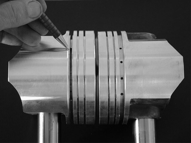 Replacement Speed Pro pistons are designed to run with tighter piston-to-wall clearance than typical forged pistons. This is largely due to the slots running the length of the piston, isolating the skirts from the crown (left). The Speed Pro race pistons are much more ridged, with drilled oil-return holes (right), and therefore need to be looser in the bores.