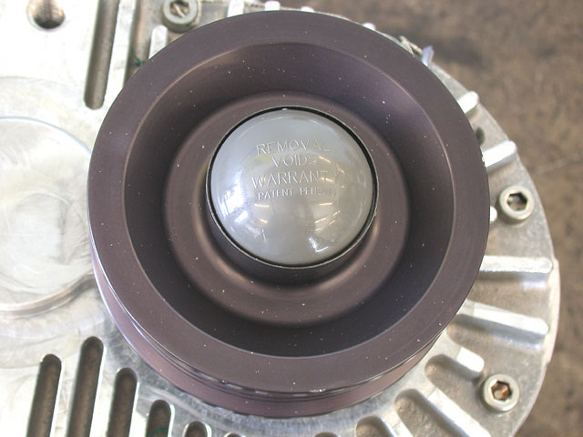 Our previously installed Steeda underdrive pulleys had to be replaced with stockers or the blower would have spun way too slowly. This could have been adjusted by altering the drive ratio of the blower with a smaller pulley, but the smog-legal kit demands the use of the factory pulley, and the pulley nut is protected with this plastic cap to prevent alteration.