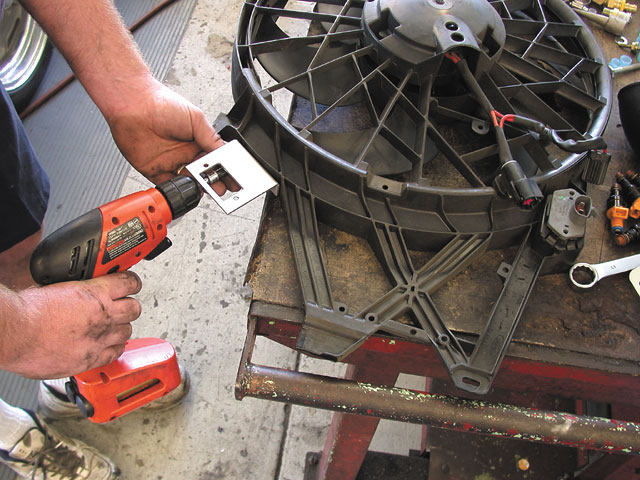 To clear the inlet ducting, the electric-fan resistor needs to be relocated, which requires screwing this new bracket to the stock shroud, grinding off the stock mounting tab, and cutting and lengthening the wires to the plug.