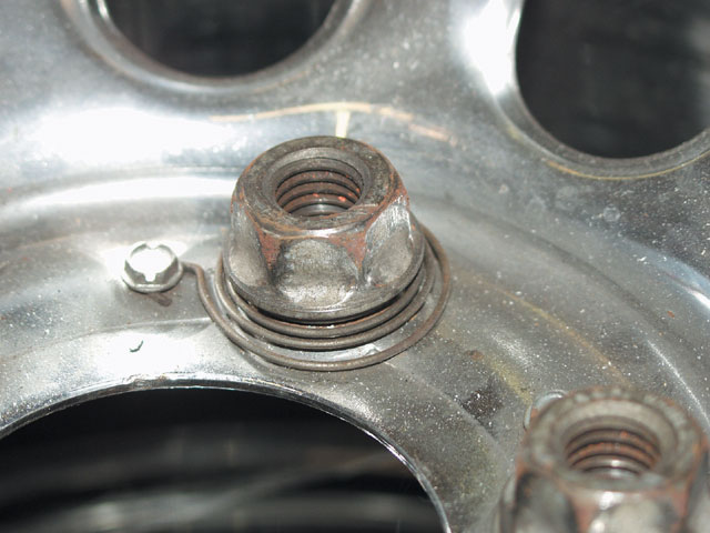 The center piece where the lug nut holes are located is visibly thicker than other non-stressed areas of the wheel. Note that the slots above the lug nut in the photo are flanged to add further strength to the center section.
