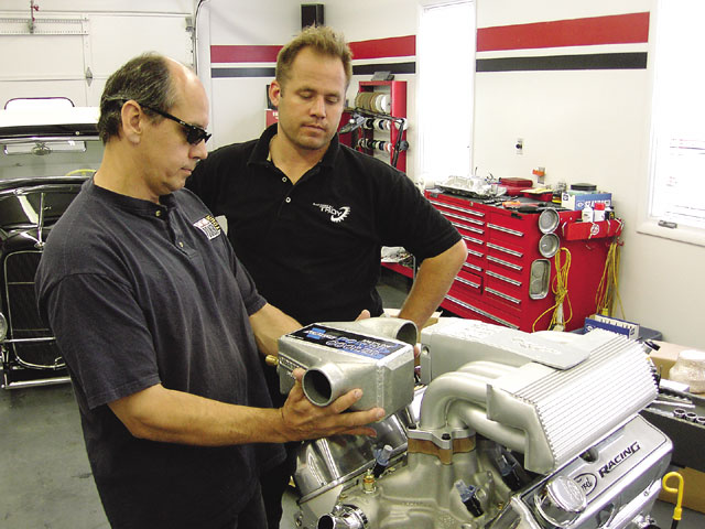 Bob Thrash (left), key source for artistic input into eBay Motors FastForward Fastback, checks out the mounting position of the Vortech Powercooler with Troy.