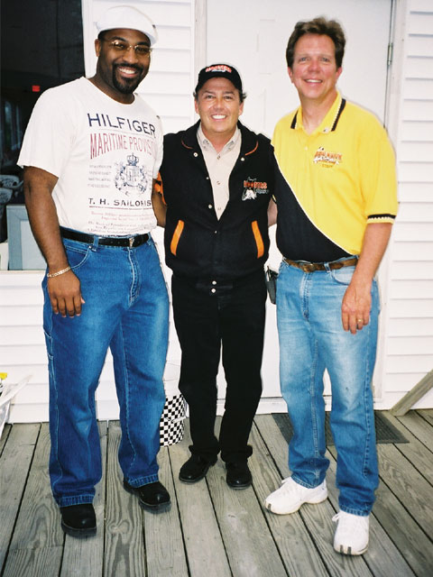 Promoter Mike Kern (right) takes the time from a Friday night to pose with NASCAR driver Brett Bodine (center) and a sponsor representative. Personal appearances like Bodine's have given Dixie Motor Speedway fans more to see and do.