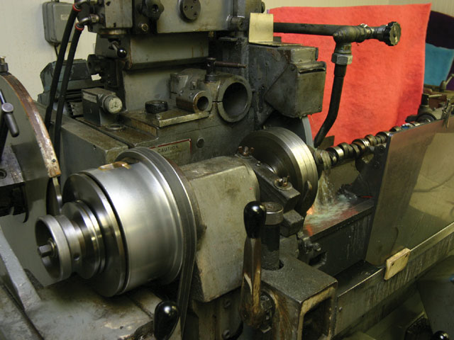 Here you can see the final setup. The master is mounted to the grinder (left) and guides an 18-inch follower. The follower and the grinding wheel are the same size and follow the same path so that the final lobe shape matches the master exactly-only on a much smaller scale. If Jones is grinding a camshaft with concave bases on the lobes, he uses a smaller 5-inch follower and grinding wheel.