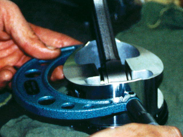 A micrometer is used to measure the piston diameter 90 degrees from the pin centerline. With this number and the expected piston-to-bore clearance, cylinder honing size can be determined.