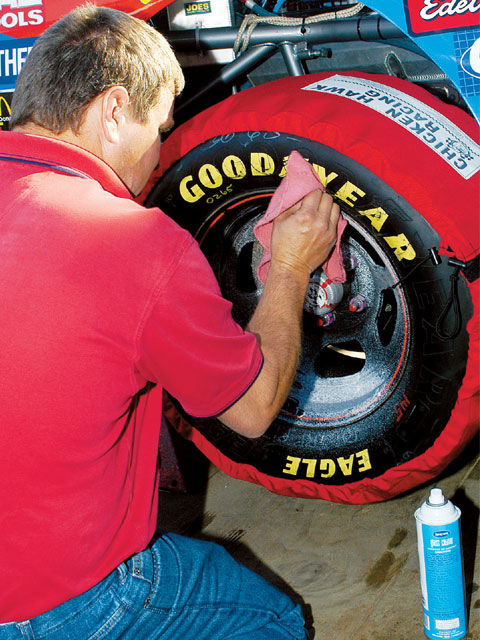 A crewmember cleans the tires already in the warmers. While the surface rubber heating is obvious, the carcass of the tire is picking up needed temperature as well.