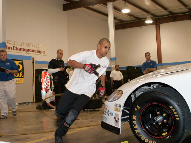 Drive for Diversity crew candidate David Cropps flies around the front bumper of the practice car during a tire-changing test.
