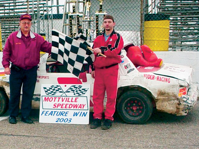 Eric Root accepts another checkered flag from track promoter Merle Holden. Root won 23 Mini Stock features in 2003.