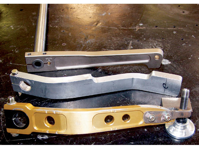 Here are three different types of sway bar arms that attach to the straight NASCAR-style sway bars. The front two are made of aluminum and will bend under a heavy load such as when used with a large-diameter sway bar. Note the black steel insert in the front arm for attaching to the sway bar. This reduces the chances of the arm stripping its spline grooves, as can happen with aluminum. The one attached to the sway bar is made of steel and flexes very little under a load. It is recommended when using a 111/42-inch or larger sway bar.