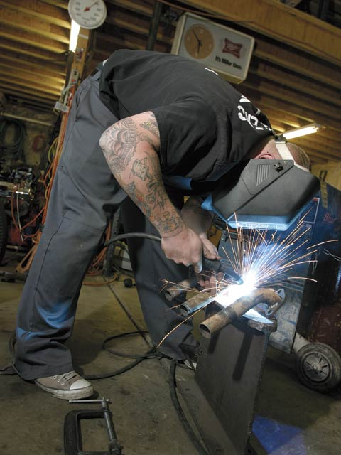 Dekon Bakker and his father Henny Bakker are the go-to guys for the sheetmetal fabrication, since that's what they do for a living. Here, Dekon is welding up a set of flathead headers.