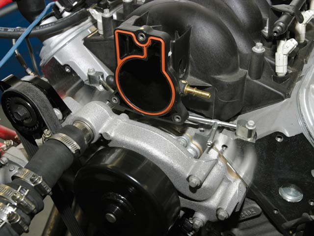 Although the LS6 manifold bolts onto an LS2, there are a couple of hitches. The water-vapor crossover tube that vents the water jackets on each side of the block gets in the way of the LS6 throttle-body. The fix was simply to swap it for an Gen III LS1/6 crossover tube (arrow), which is a direct retrofit. We also had to relocate the driver-side coil-pack bracket to clear the LS6 fuel-rail inlet fitting.
