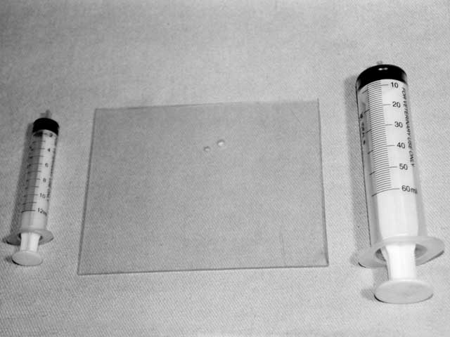 To accurately measure intake port and combustion-chamber volume, wepurchased two graduated syringes--one measuring 60 cc and the other 12cc--from our local animal feed store. The plastic sheet in the middlewas used to cover the port or chamber while fluid was injected. Precisemeasurements allow for accurate calculations of variables such ascompression ratio and cross-sectional port area.