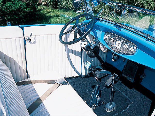 Inside, there's a Stewart-Warner speedboat panel and a Bell-type, four-spoke steering wheel with a tach on the column.  Ron custom-made the seat and upholstered the interior in white Naugahyde with a black tweed carpet. A neat tan canvas top is part of this car's signature.