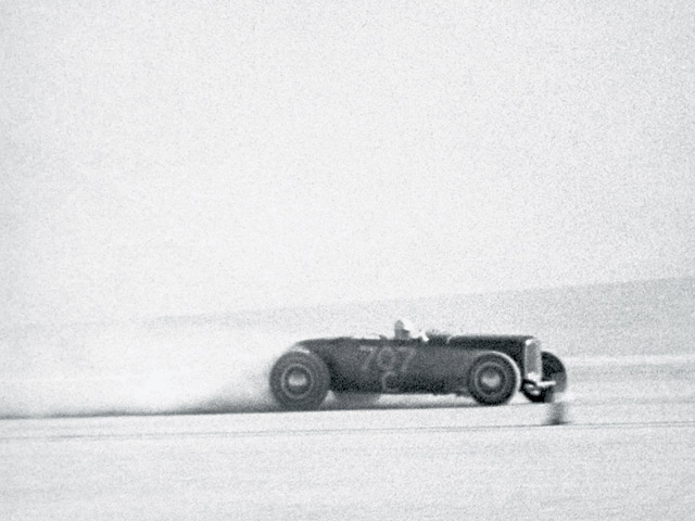 Jim Khougaz campaigned his '32 roadster successfully at El Mirage from 1946-1950. At first, it was a dual-purpose street and lakes car, but by 1949, with a tank full of methanol and a full bellypan, it could top 140 mph. Here, Khougaz streaks across the lakebed at El Mirage in a period photo that captures the excitement of lakes racing and preserves it for all time.
