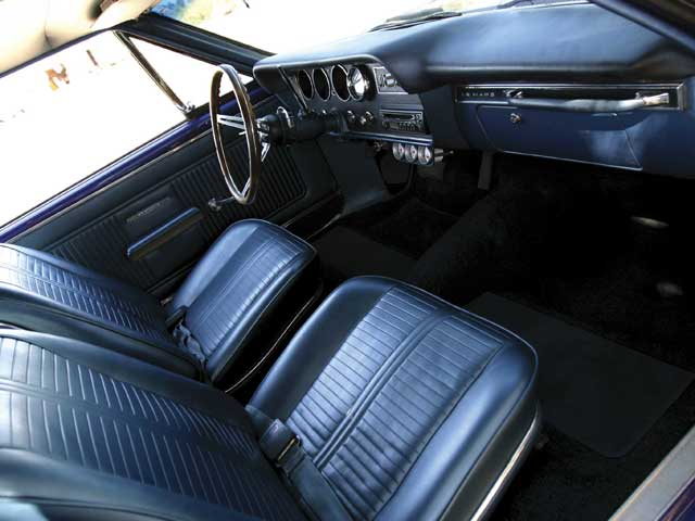 Craig's Upholstery in Phoenix restored the medium-blue bucket seat interior to stock with a headliner, carpet, and upholstery kit from Year One. Mods are limited to the steering wheel, the Rockford Fosgate stereo with visor-mounted controls, the kick panel and the floor-mounted speakers, Auto Meter gauges under the dash and a Sun tach in it. Even the column shift remains.