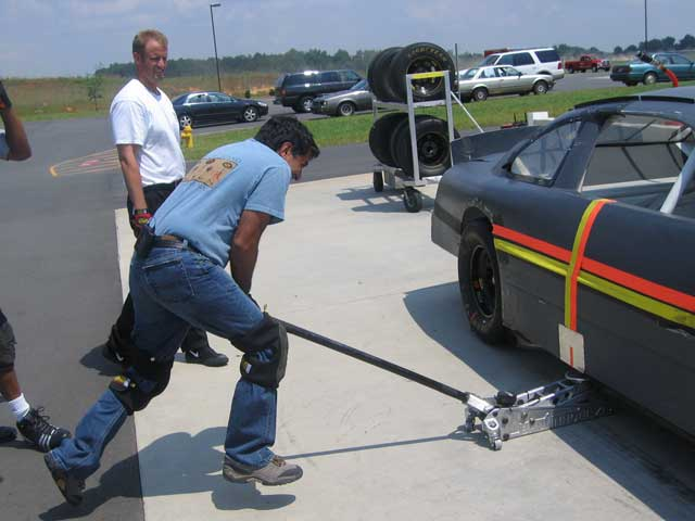 Dr. Sanjay Gupta tries his hand at being a jackman during pit crew practice.