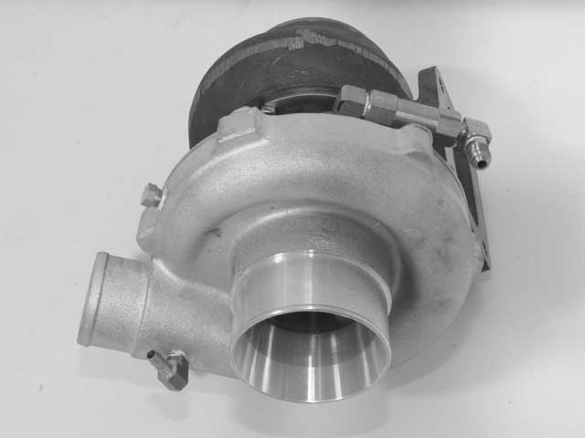 The Garret T04E turbocharger comes assembled from STS. Teflon tape is utilized to seal the supplied brass fittings. After ensuring the tape doesn't protrude past the threads, a 90-degree elbow is installed on the compressor side (bottom left) for wastegate boost control, and another 90-degree elbow, oil check valve (pressure switch), and 90-degree elbow install in the center for the turbine shaft.