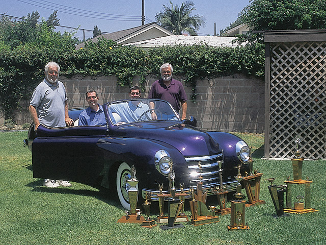 The gang's all here. The fresh Fadeaway Ford with (from left to right): Bob Trousil, the car's restorer; Lance and Jay Bergman, the car's owners; and Bud Lehner, the car's original owner. Original trophies won by Bud at car shows are seen in the foreground.