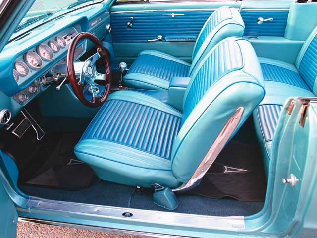 A brace of Auto Meter dials have been incorporated into the dash to monitor the engine, while both the tilt column and the steering wheel from Flaming River offer comfort on the road. The carpet is from ACC, but the remainder of the interior was customized by Scooter Morris of Scooter's Upholstery in Cedar Point, North Carolina. The original seat covers and door panels were used as patterns for the custom replacements,