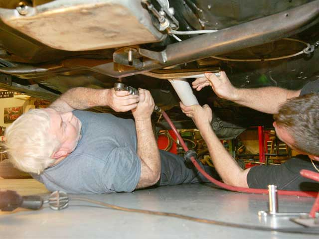 Gear specialist Jim Cook and car owner Chris Hargett remove the exhaust pipes, driveshaft, and crossmember before getting to work on the transmission.