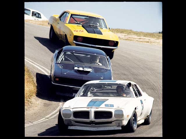 Here Jerry Titus' #8 Firebird (the production Trans Am's hood scoop was declared illegal) leads Swede Savage's #42 'Cuda and Milt Minter's year-old #68 Camaro down Laguna Seca's corkscrew during the season's first race. Milt Minter pulled off the year's greatest upset with a Camaro win at Donnybrooke.