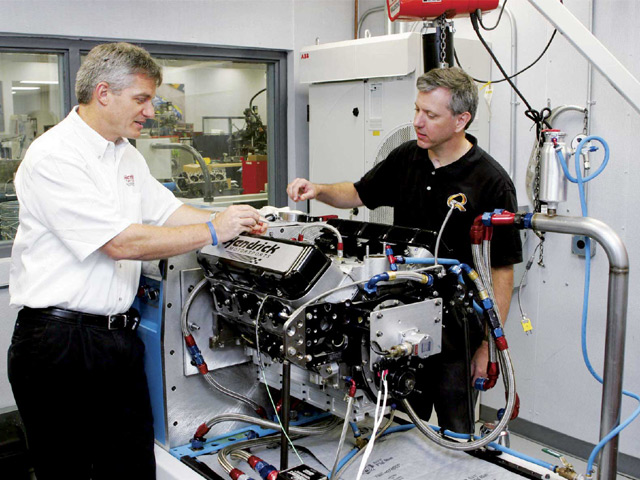 Hendrick Motorsports' Dr. Andrew Randolph and Quaker State's motorsports lead, Paul Bastien, discuss ideas while testing a complete race engine in this fixture, which measures friction losses inside the engine.