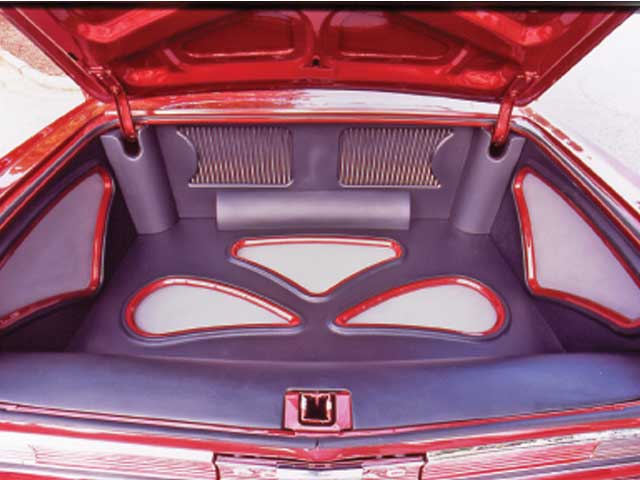 The stereo's output is boosted by JL 500/1 and 300/4 amps mounted in the trunk under a custom cover. A pair of JL W-7 8-inch subwoofers are also in the trunk behind custom grillework.