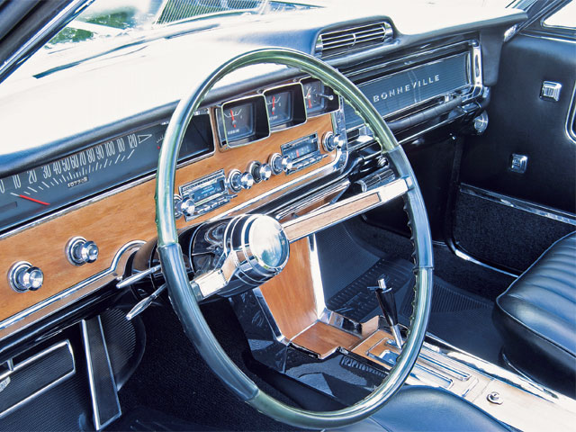 The driver is surrounded by a panorama of real walnut veneer, while the raucous 421 engine is monitored courtesy of the optional gauge cluster that features oil pressure and engine temperature gauges in the center instrument panel, and gasoline and amp gauges, and a clock angled toward the driver over the optional AM/FM radio with reverb.