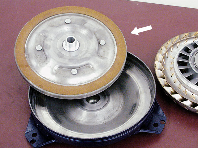 A lockup converter uses a clutch plate (arrow) with friction material that locks up against the converter housing while the plate is splined to the transmission input shaft. This eliminates torque-converter slippage and improves mileage.