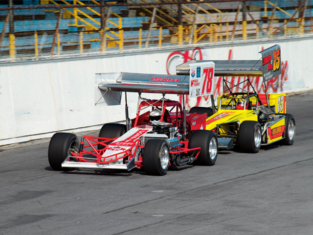 In these photos, we see the wing is at a high angle of attack entering the turns and lying flat on the straightaways. Mark Sammut, No. 78, leads Liquid Lou Cicconi, No. 75, down the front stretch at Oswego. Note the flat position of the wings.
