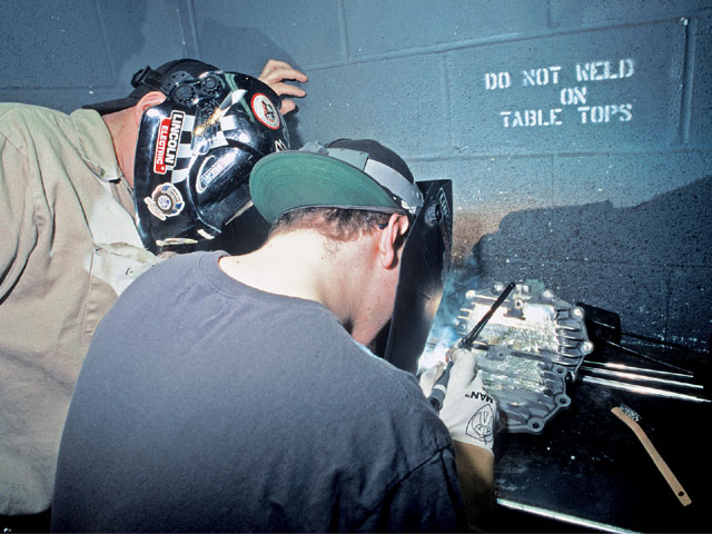 They're right there with you. An instructor watches as a student welds magnesium. He's actually welding two scrap quick-change covers together.