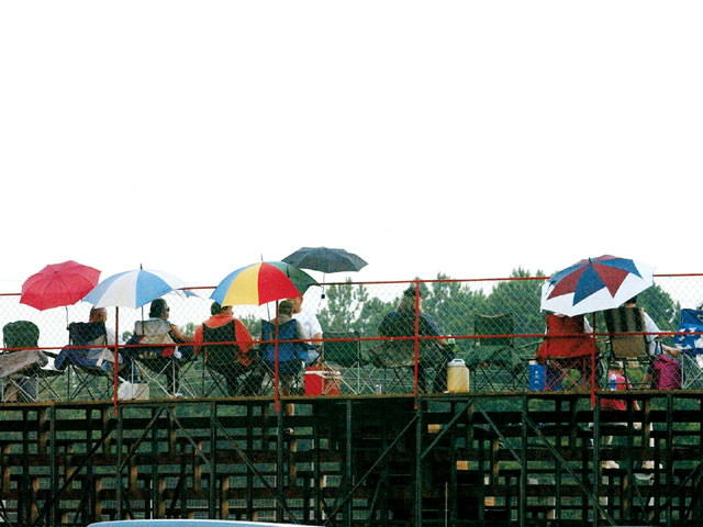 The fans were warding off the temperature with umbrellas, which were not needed for rain.