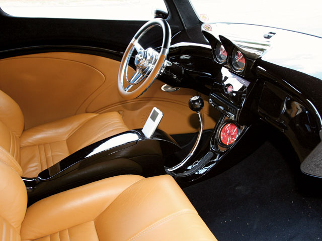 A better view of the shifter shows how the shape follows the console as it flows into the dash. Classic Instruments is responsible for the one-off red and black gauges, while the Flaming River tilt steering column got topped off with a modified Colorado Custom steering wheel.