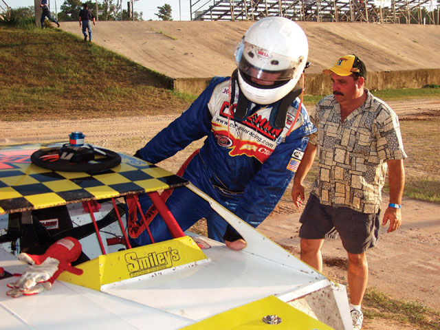 Dalton Zehr prepares for practice in the Circle Track Modified car as his dad, Marty, looks on. Although Dalton got up to speed quickly, he admits he needs more seat time before being capable of winning.