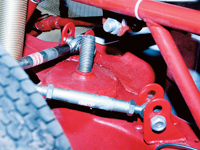 The cars that use stock springs have weight jacking screws at the front and rear that are mounted with a housing welded to the frame to adjust the height of the top of the spring. The top of the screw has a square hole to fit a 1/2-inch drive extension. A mark should be painted on one side of the screw so the number of turns can be easily counted.