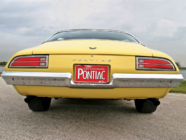 Sans the D80 rear air spoiler, this yellow 'Bird flies under the radar and is often mistaken for a low-performance Firebird. Clues to its alter ego can be garnered by the twin, reproduction, chrome exhaust-pipe extensions. The taillight lenses, rear bumper, and emblems are all original, as is the trunk weatherstripping.