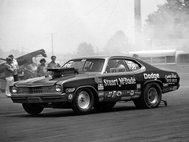 The cigar-clenching driver is unmistakably Dick Landy, but the name Stuart McDade may be known to but a few Mopar drag racing fans. Stuart was a stalwart Mopar racer and sometimes Chrysler test driver from the southeast. His Demon was closely built to Dick's, so when Dick's Demon was involved in a midseason crash, he turned to Stuart, who arranged to loan his car so Dick could keep his major race date commitments. That loaner car, with a Landy 426 Hemi powertrain transplant, provided a stop-gap while Dick's new Demon was being built in his Northridge, California, shop. A local sign painter provided a quick window sign to identify the driver as Dick Landy, shown here in action at the NHRA Springnationals at National Trail Raceway, outside Columbus, Ohio.
