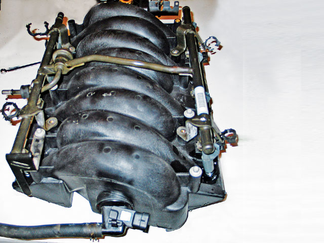 We swapped all the parts (injectors, fuel rails, brackets, hoses, and throttle body) from the LS1 manifold to the LS6 without any modifications. (It's important to attach the power-brake hose, shown connected to the vacuum port, at the back of the manifold.) The back of the manifold also has a connection for manifold vacuum and the MAP sensor. We will connect them before the intake is bolted in place, because once its bolted on, we can't get our hands back there.