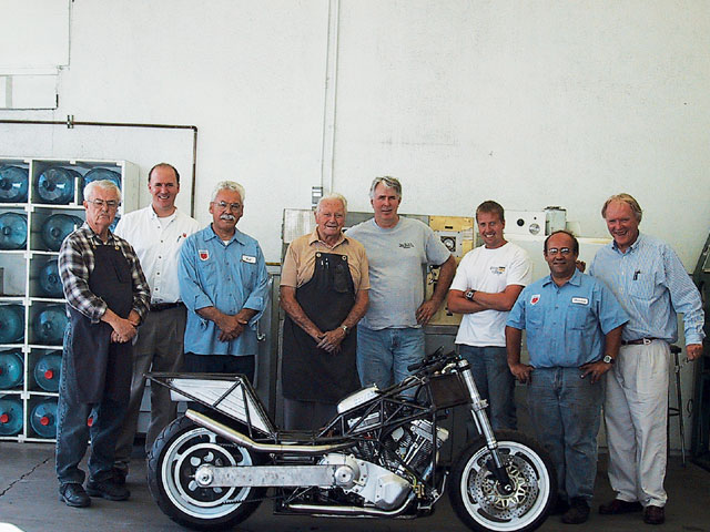 All American Racers introduced the latest version of the Alligator motorcycle in 2006. Its S & S V-twin engine will have 111 or 124ci. Gurney is at right. Hot rodding legend Phil Remington in the shop apron (center) has been with All American Racers since its founding decades ago. Before that, he was with Carroll Shelby during the Cobra years. Also pictured (from left) are Butch Wilson, Justin Gurney, Bob Marker, Remington, Steve Kilgore, Stevo Jacobs, Howard Monise, and Dan Gurney.