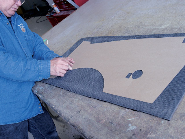 Kirby Kendall traces a chipboard pattern of the firewall panel onto carpeting.